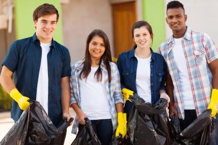 juventud: alegres jóvenes voluntarios adolescentes con bolsa de basura Foto de archivo