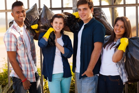 group of smiling teenage volunteers with garbage bags after cleaning the streets photo