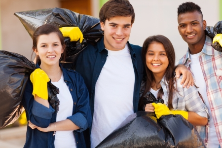 cheerful young volunteers with garbage bag after cleaning the streets photo