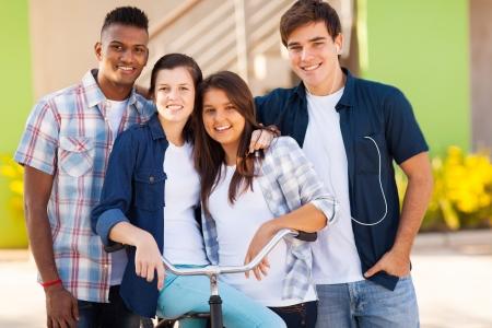 adolescencia: feliz grupo de estudiantes de secundaria con una bicicleta al aire libre Foto de archivo