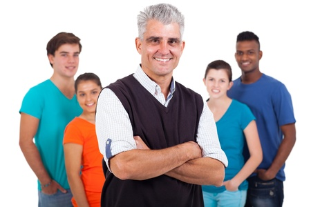 happy middle aged teacher with arms folded in front of high school students isolated on white background Stock Photo - 20235339