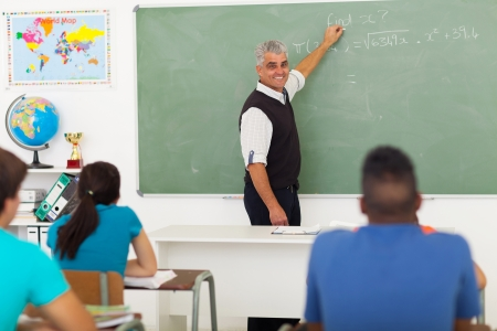 cheerful middle aged teacher teaching high school mathematics in classroom photo