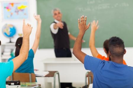 aula: grupo de estudiantes con las manos en alto en el aula durante la lecci�n