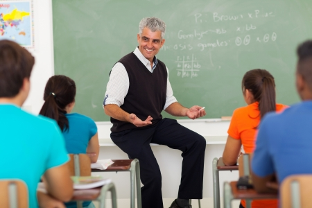 friendly male teacher explaining lesson to students in classroom photo