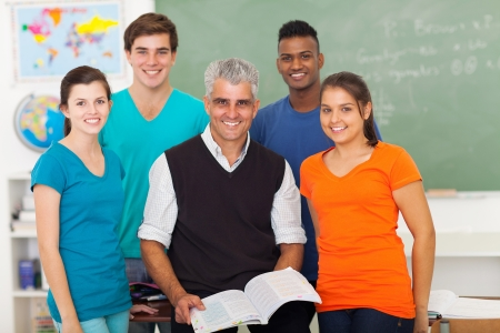 student girl: group of cheerful high school students in classroom with senior teacher