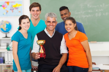 senior teacher and group of high school students holding trophy in classroom photo