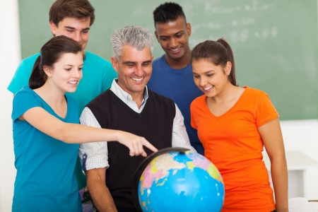group of happy high school students and teacher looking at globe Stock Photo - 20235270