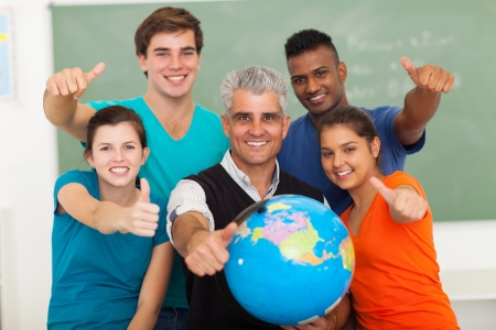 high school student: group of  high school geography students and senior teacher giving thumbs up in classroom