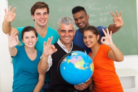 estudiantes adultos: alegres estudiantes de geografía de secundaria y maestros que dan la muestra aceptable de la mano en el aula Foto de archivo