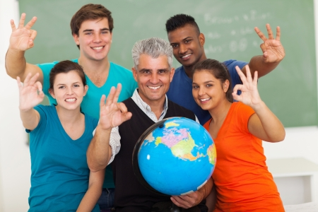 cheerful high school geography students and teacher giving ok hand sign in classroom photo