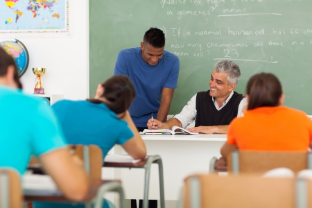 smiling middle aged teacher helping a high school student in classroom photo