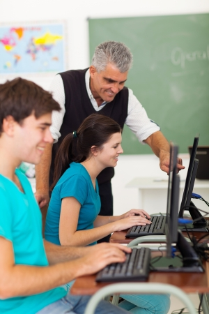 learners: cheerful middle aged teacher helping high school students with computer work