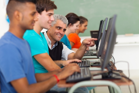 school aged: happy male senior teacher helping student with computer Stock Photo