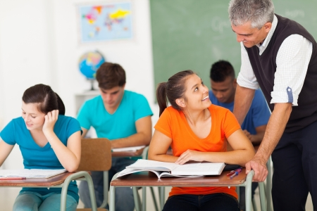 estudantes: sorrindo professor colegial que fala ao estudante na sala de aula