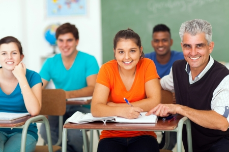 cheerful high school teacher with group of students in class