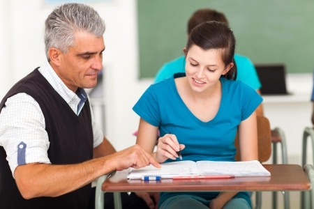 learners: mature high school teacher helping a student with her classwork