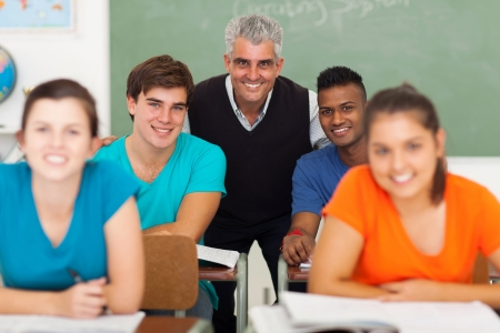 happy middle aged high school teacher with group students in classroom photo