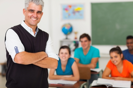 school aged: smiling middle aged high school teacher with arms folded standing in front of the class Stock Photo