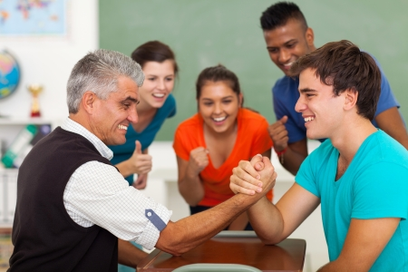 friendly middle aged teacher arm wrestling with high school student in classroom during break photo