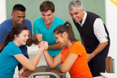 cheerful female high school students playing arm wrestling in classroom photo