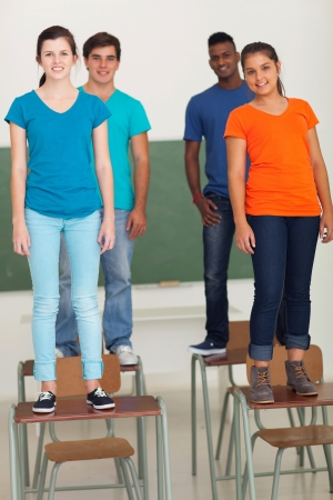 group of casual high school students standing on top of desks  photo