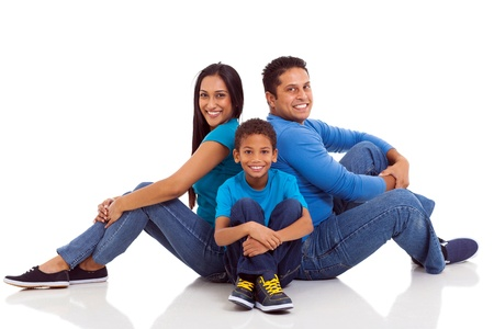 woman sitting floor: happy indian family sitting on the floor isolated on white Stock Photo