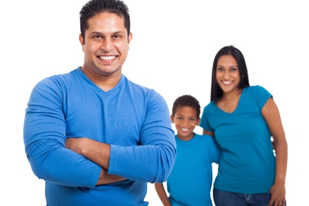handsome indian father with arms crossed in front of family photo