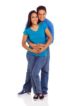 pareja abrazada: sonriente joven pareja india que abarca en el fondo blanco
