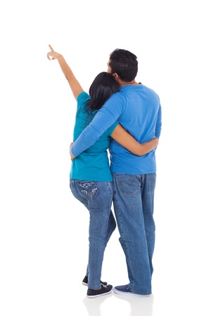 indian couple: rear view of young couple pointing at copy space over white background
