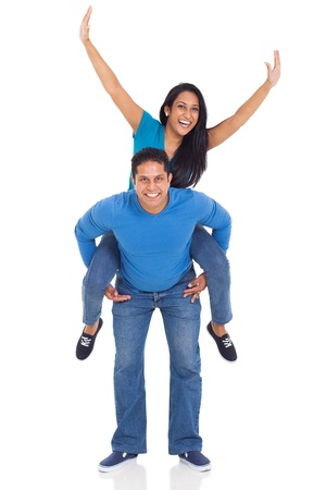 portrait of loving indian couple having fun with piggyback ride isolated over white background photo