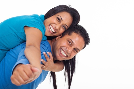indian family: happy young indian couple having fun with piggyback on white background