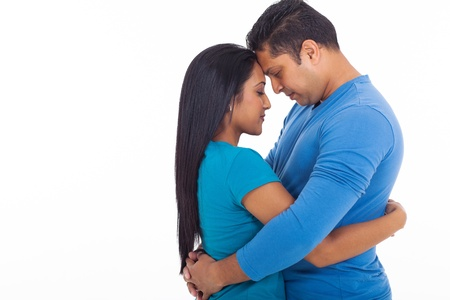 loving young indian couple hugging with eyes closed on white background photo
