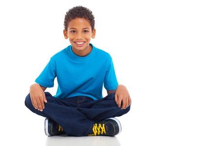 Leuke Afrikaanse Amerikaanse jongen zittend op een witte achtergrond