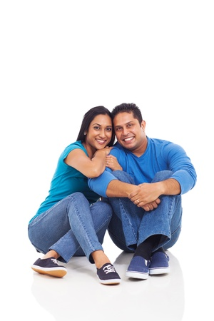 cute young indian couple sitting on the floor isolated on white photo