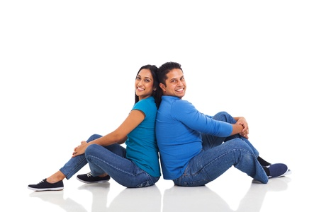 cheerful young indian couple sitting back to back on floor photo