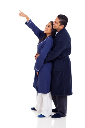 smiling indian couple in nightgowns pointing at copy space on white background photo