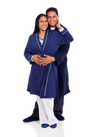 young indian couple in pajamas embracing isolated on white photo