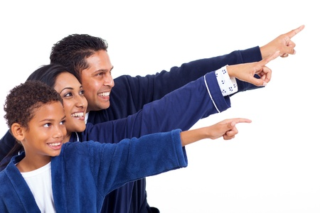 happy indian family in nightclothes pointing empty copy space on white background photo