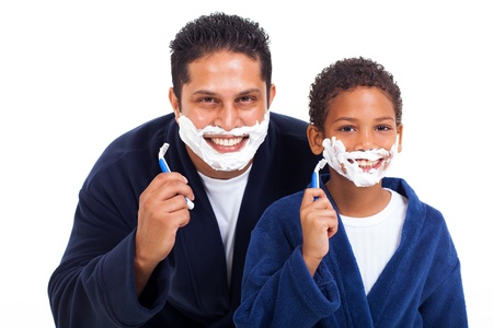 playful little indian boy shaving with father isolated on white
