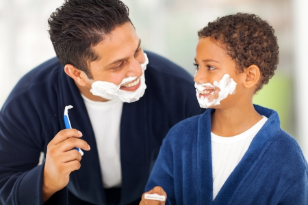 playful father and son shaving together at home bathroom photo