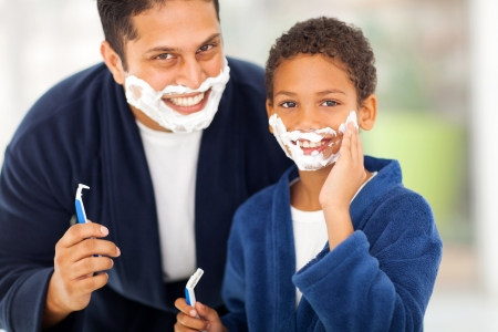 happy son playing with fathers shaving foam at home photo