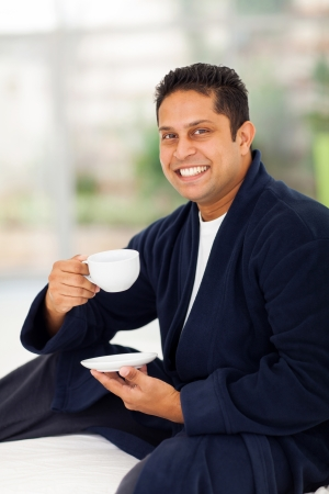 cheerful indian man in pajamas drinking coffee on bed photo