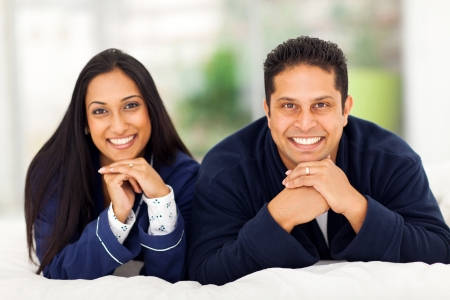 portrait of happy indian couple lying on bed photo