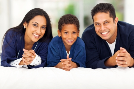 nightclothes: cheerful indian family lying on bed together Stock Photo