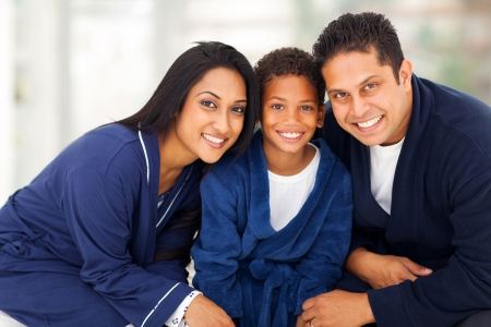 nightclothes: cute young indian family in their nightclothes sitting on bed  Stock Photo