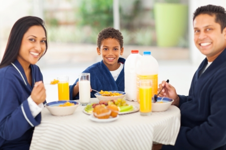 happy indian family having breakfast together at home photo