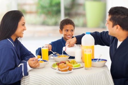 loving father pouring milk in his sons corn flakes during breakfast photo
