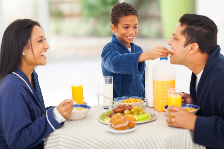 cute little indian boy feeding his father fruit on breakfast table photo