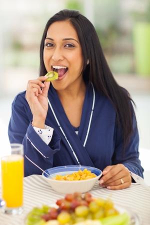 kiwifruit: pretty indian woman eating kiwifruit during breakfast