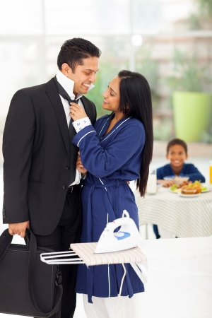 loving wife helping husband with his tie before he going to work photo